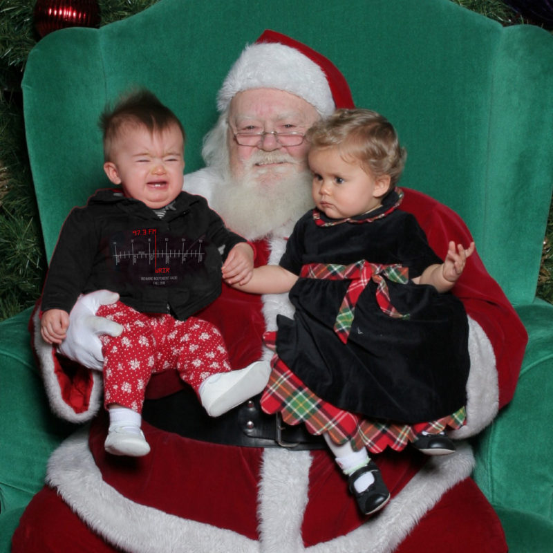 2 kids sitting on Santa's lap and one is crying